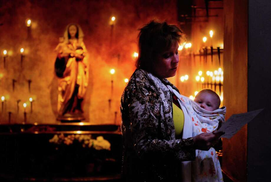 C.J. Walker Waite mirrors the Virgin Mary as she holds her son, Zachary Walker Waite, 8 months while she sings from the program during a prayer service at St. James Cathedral for the victims of of the May 30, 2012, shootings. Photo: LINDSEY WASSON / SEATTLEPI.COM
