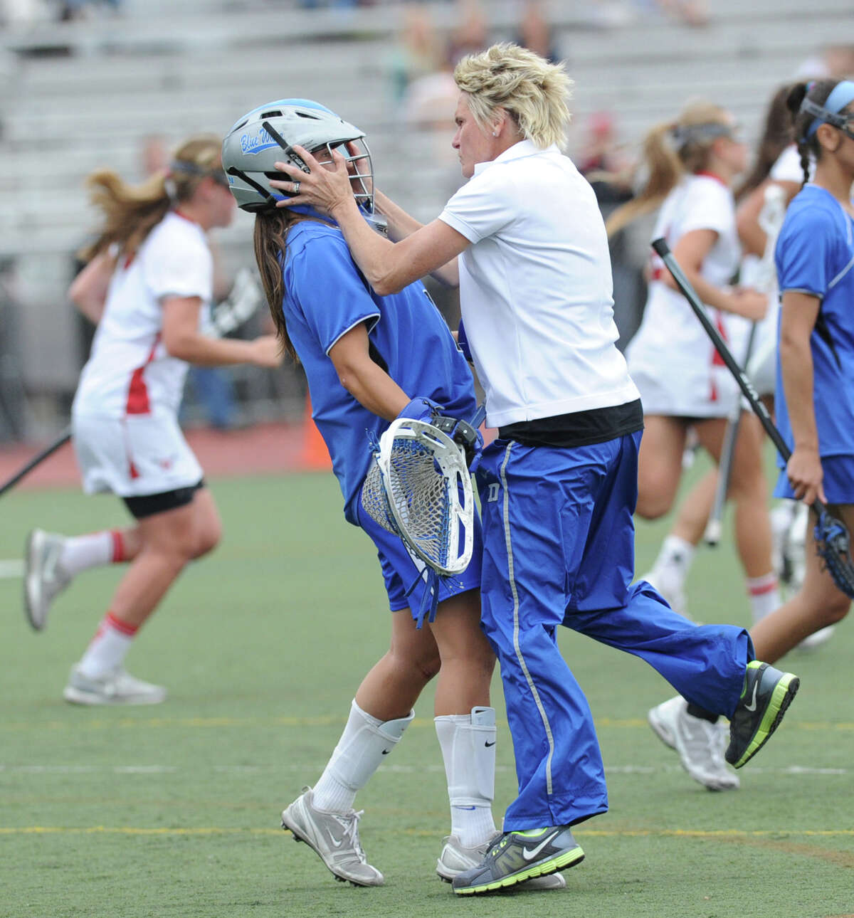 Darien High School girls lacrosse coach Lisa Lindley, right, grabs her goalie Caylee Waters during a timeout in the first half of the FCIAC girls lacrosse finals between Greenwich High School and Darien High School at Brien McMahon High School in Norwalk, Friday, May 25, 2012. Darien won the championship over Greenwich 17-14.