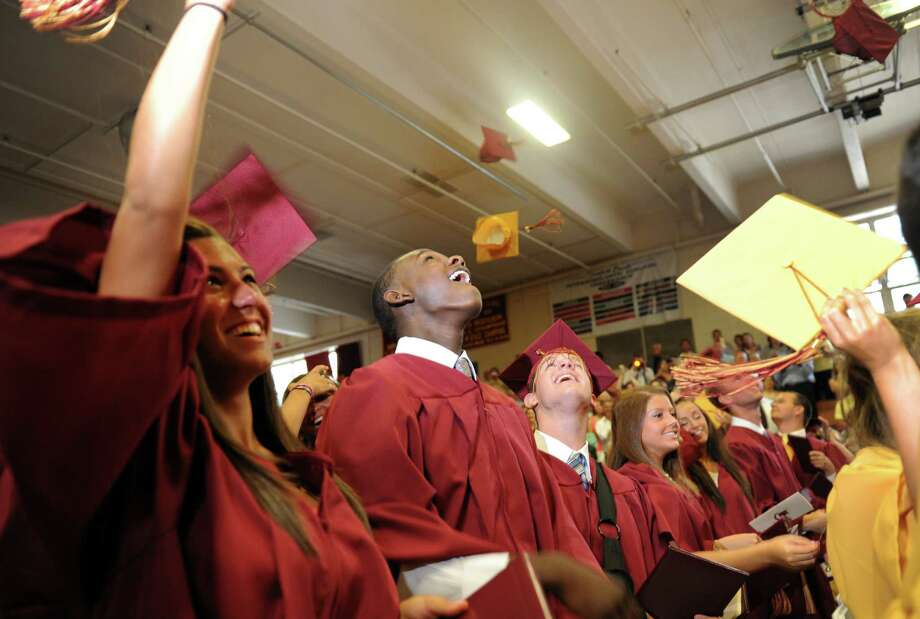St. Joseph High School graduates Courtney Iassogna, Timajh Parker-Rivera and Jason Holcomb throw their caps in the air during commencement exercises Saturday, June 2, 2012 at the school in Trumbull, Conn. Photo: Autumn Driscoll / Connecticut Post