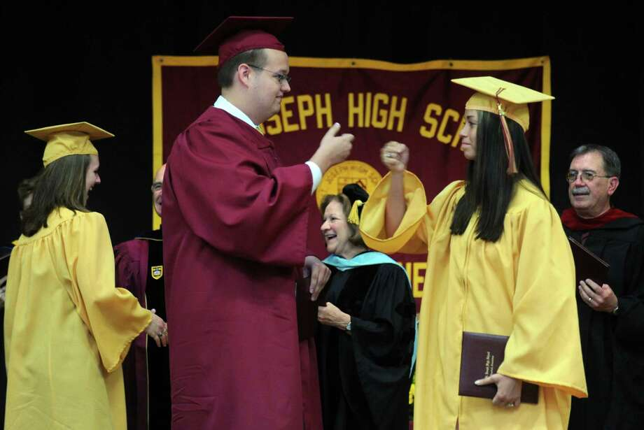St. Joseph High School graduates Matthew Gaynor, of Milford, and Kayla Giampaolo, of Shelton, bump fists during commencement exercises Saturday, June 2, 2012 at the school in Trumbull, Conn. Photo: Autumn Driscoll / Connecticut Post