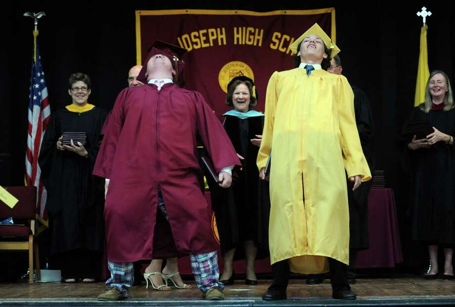 "St. Joseph High School graduates Alec Lessard, left, and Eddie Lockwood, both from Shelton, shout ""dance party"" during commencement exercises Saturday, June 2, 2012 at the school in Trumbull, Conn.  The senior class responded with a spontaneous group shimmy. Photo: Autumn Driscoll / Connecticut Post"