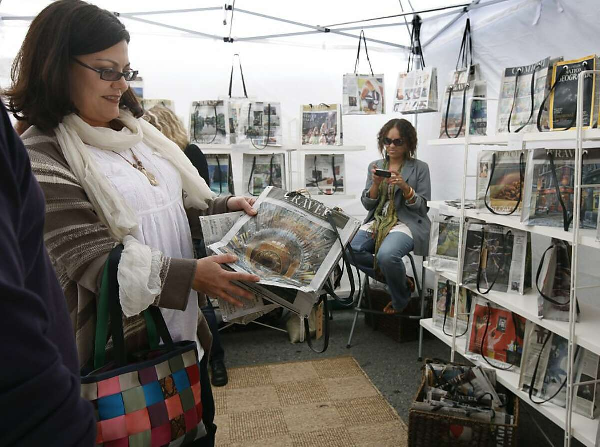 Chris Harrison chooses from a selection of handbags made from old newspapers at the Union Street Festival in San Francisco, Calif. on Saturday, June 2, 2012.