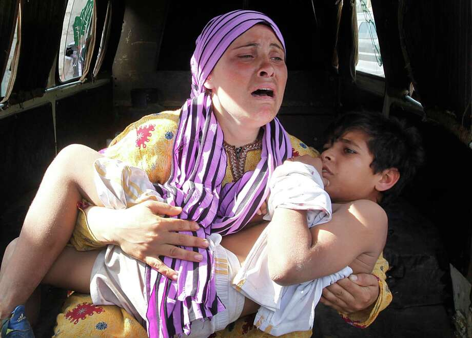 A Syrian woman cries as she carries her wounded son, who was shot in the hand by a Syrian border guard while crossing a river into Lebanon on Wednesday. Photo: Hussein Malla / AP