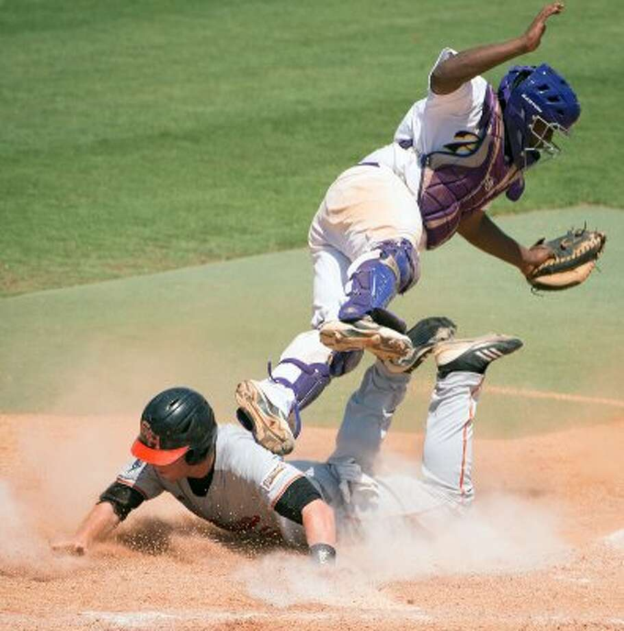 Sam Houston State second baseman Jessie Plumlee slides safely into home as Prairie View catcher Evan Richard tumbles over him during the ninth inning of an NCAA college baseball tournament regional game Saturday, June 2, 2012, in Houston. Sam Houston State won the game 4-2. ( Smiley N. Pool / Houston Chronicle ) (Smiley N. Pool / Houston Chronicle)