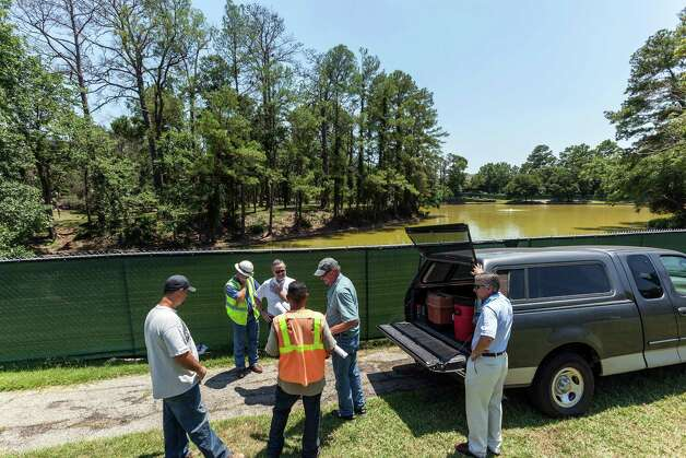Unidentified workers gather at Lake Thicket on Friday. The site, located in the 15000 block of Memorial Drive, has been fenced off and may be drained by new developers, which has upset neighbors in the area. Photo: Craig Hartley / Copyright: Craig H. Hartley