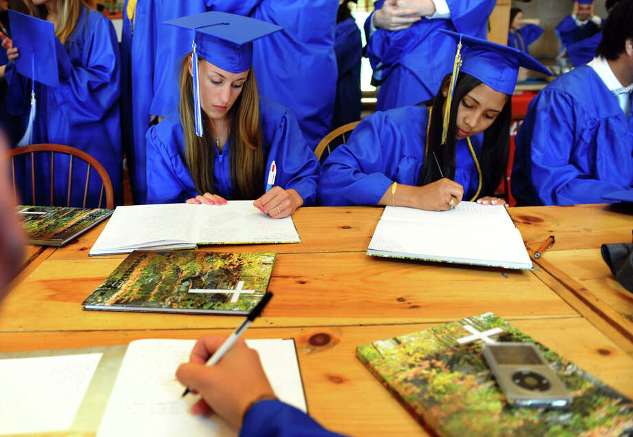 Soon-to-be graduates Sara Phillips, left, and Paola Medrano sign some yearbooks before the start of Christian Heritage School's 29th Annual Commencement Exercises in Trumbull, Conn. on Saturday June 2, 2012. Photo: Christian Abraham / Connecticut Post