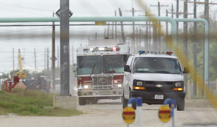 A Harris County Medical Examiner's van and a Channelview fire truck leave the Oiltanking Partners plant, where a welding accident sparked an explosion. Photo: Melissa Phillip / © 2012 Houston Chronicle