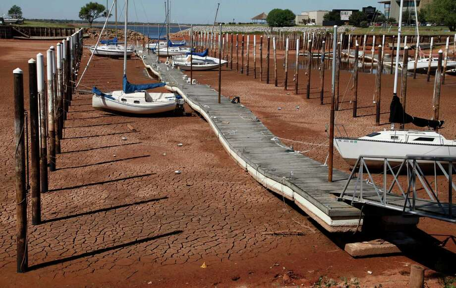 Sailboats and a floating dock lie on the dry, cracked dirt in a harbor at Lake Hefner in Oklahoma City. This July was the hottest month in a century. Yes, the heat is on for climate-change skeptics. Photo: Associated Press