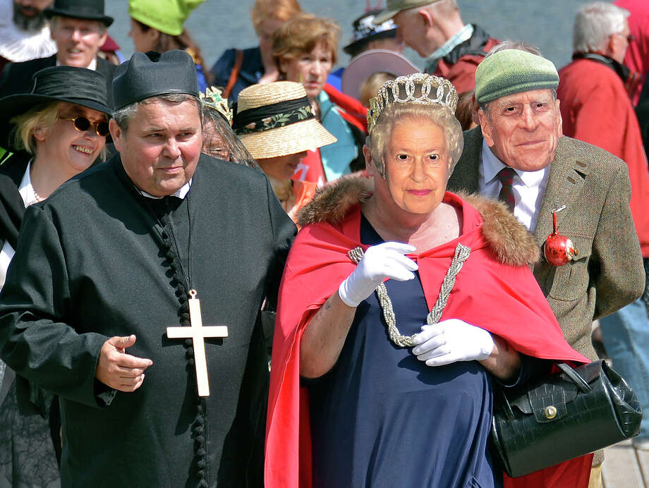 Participants in a comical parade are dressed as Britain's Queen Elizabeth II, centre, with Prince Philip, right, as the British-German club Duisburg celebrates the Queen's Diamond Jubilee that marks the 60th anniversary of Queen Elizabeth's accession to the throne with a comical parade and a picnic on a float on a lake in Duisburg, western Germany, Saturday, June 2, 2012. Photo: Martin Meissner, Associated Press / AP