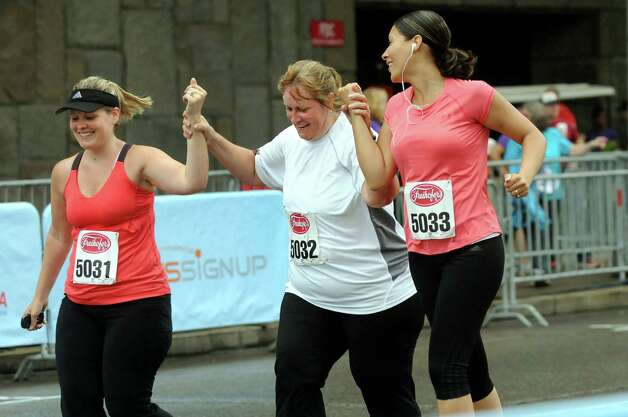 Jodee Citrolo of Castleton, center, crosses the finish line with her daughter Kellie Valenti of Clifton Park, left, and her daughter-in-law Mariella Peters of Herkimer during the Freihofer's Run for Women on Saturday, June 2, 2012, in Albany, N.Y. It was Citrolo's first time running in the race after years as a spectator. (Cindy Schultz / Times Union) Photo: Cindy Schultz / 00017846B