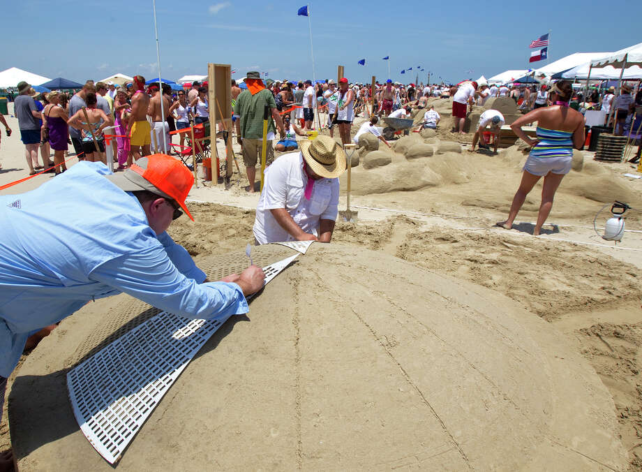 Mike Binick, left, and Mike Valenzuela, center, work on their sand sculpture resembling the Astrodome during the 26th annual AIA SandCastle Competition on Galveston's East Beach Saturday, June 2, 2012, in Galveston. Photo: Cody Duty, Houston Chronicle / © 2011 Houston Chronicle