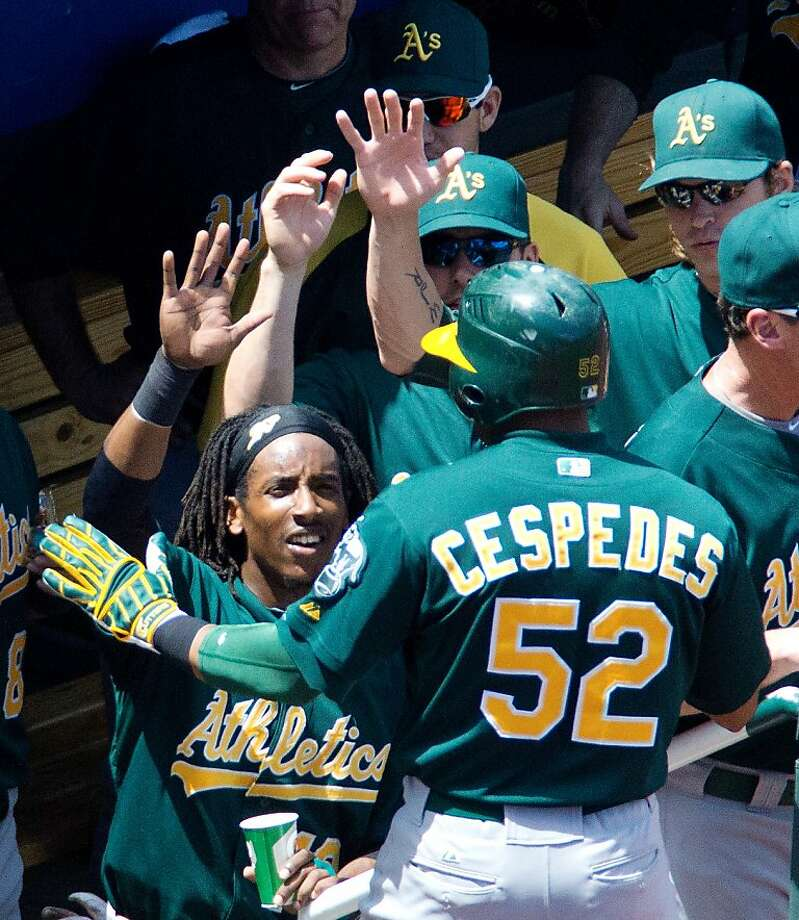 The Oakland Athletics' Yoenis Cespedes (52) is congratulated at the dugout steps after scoring on an RBI double by Kila Ka'aihue in the fifth inning against the Kansas City Royals on Saturday, June 2, 2012, at Kauffman Stadium in Kansas City, Missouri. The A's won, 9-3. (John Sleezer/Kansas City Star/MCT) Photo: John Sleezer, McClatchy-Tribune News Service