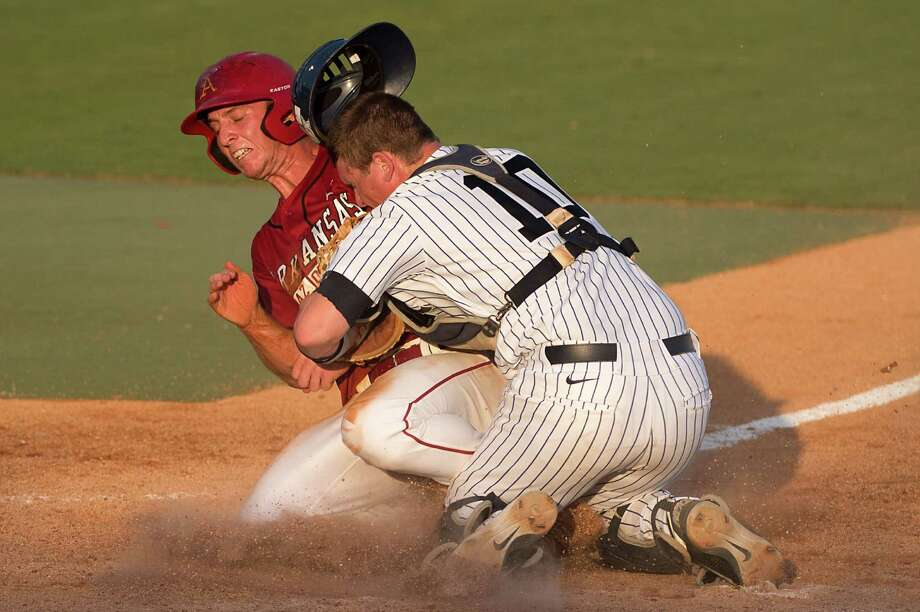 Arkansas' Tim Carver is out at home in a collision with Rice catcher Craig Manuel during the sixth inning of an NCAA college baseball tournament regional game Saturday, June 2, 2012, in Houston. Photo: Smiley N. Pool, Houston Chronicle / © 2012  Houston Chronicle
