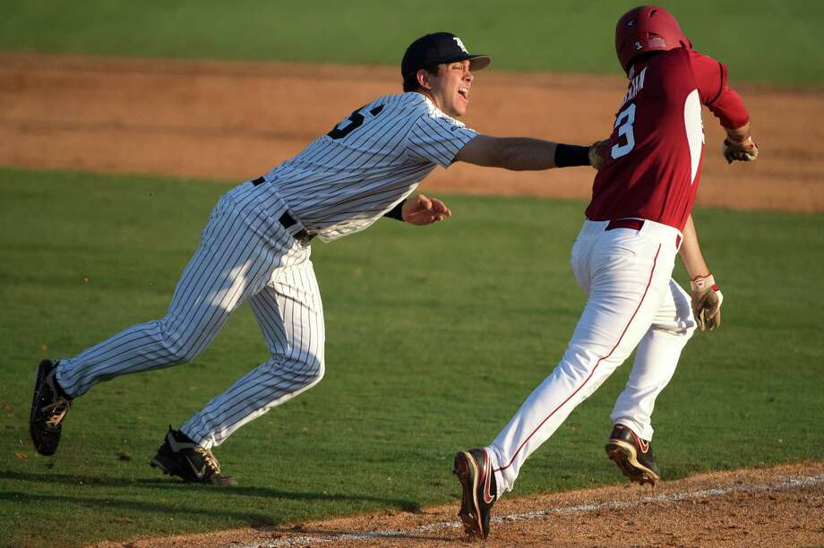 Rice first baseman Ryan Lewis puts a tag on Arkansas' Jacob Mahan (3) on a bunt attempt during the sixth inning of an NCAA college baseball tournament regional game Saturday, June 2, 2012, in Houston.  Arkansas won the game 1-0. Photo: Smiley N. Pool, Houston Chronicle / © 2012  Houston Chronicle