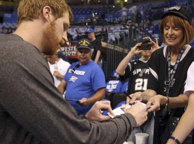 San Antonio Spurs' Matt Bonner, left, signs an autograph for Spurs fan Judith Laird, right, as her son, Brennus, center, uses a camera phone before the first half of game four of the NBA Western Conference Finals in Oklahoma City, Okla. on Saturday, June 2, 2012.  The Lairds are from San Antonio. (San Antonio Express-News)