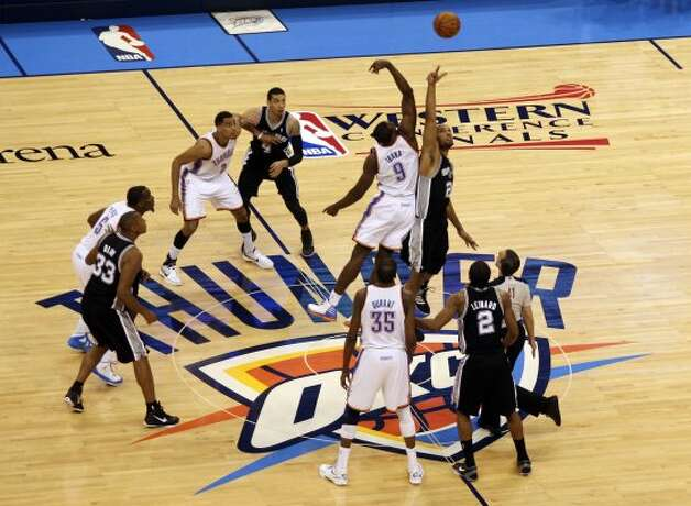 San Antonio Spurs' Tim Duncan (21) jumps for the tip against Oklahoma City Thunder's Serge Ibaka (9) during the first half of game four of the NBA Western Conference Finals in Oklahoma City, Okla. on Saturday, June 2, 2012. (Kevin Martin  / San Antonio Express-News)