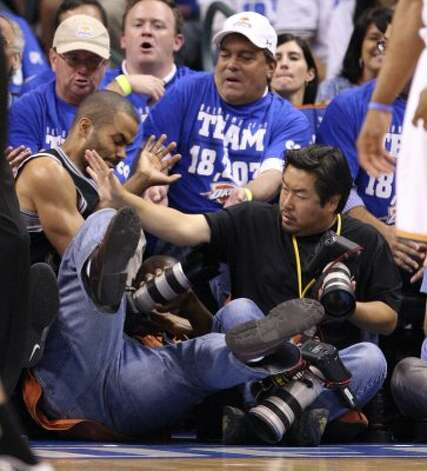 San Antonio Spurs' Tony Parker (9) falls over photographers during the first half of game four of the NBA Western Conference Finals in Oklahoma City, Okla. on Saturday, June 2, 2012. (Edward A. Ornelas / San Antonio Express-News)