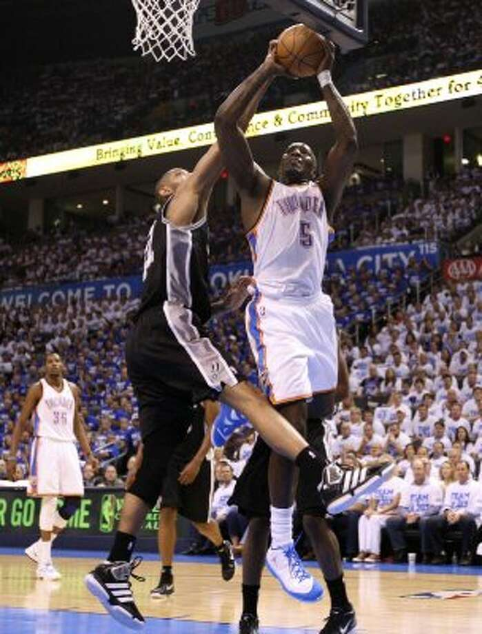Oklahoma City Thunder's Kendrick Perkins (5) goes up for a basket against San Antonio Spurs' Tim Duncan (21) during the first half of game four of the NBA Western Conference Finals in Oklahoma City, Okla. on Saturday, June 2, 2012. (Edward A. Ornelas / San Antonio Express-News)