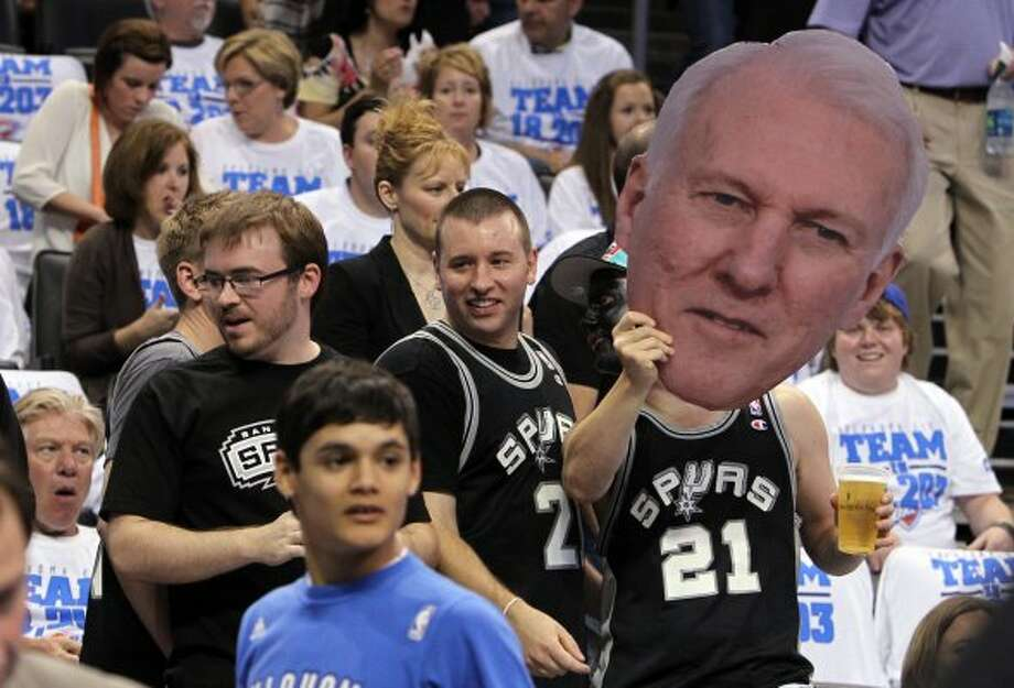 Spurs fans Spencer Becker, left, and Chris Carey, both of Kansas City, stand next to another Spurs fan with a sign during the first half of game four of the NBA Western Conference Finals in Oklahoma City, Okla. on Saturday, June 2, 2012.