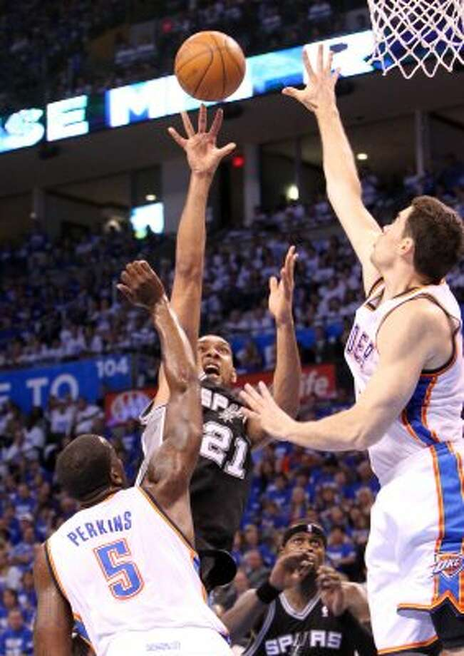 San Antonio Spurs' Tim Duncan (21) shoots against Oklahoma City Thunder's Kendrick Perkins (5) and Oklahoma City Thunder's Nick Collison (4) during the first half of game four of the NBA Western Conference Finals in Oklahoma City, Okla. on Saturday, June 2, 2012. (Kin Man Hui / San Antonio Express-News)