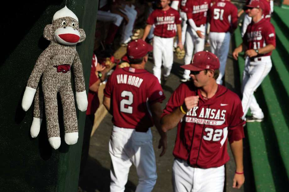 A rally monkey hangs in the Arkansas dugout as the Razorbacks take on Rice in an NCAA college baseball tournament regional game Saturday, June 2, 2012, in Houston. Arkansas won the game 1-0. Photo: Smiley N. Pool, Houston Chronicle / © 2012  Houston Chronicle
