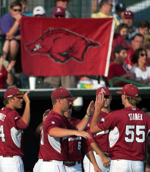 Arkansas pitcher Ryne Stanek (55) is congratulated by teammates after getting the final out of the t