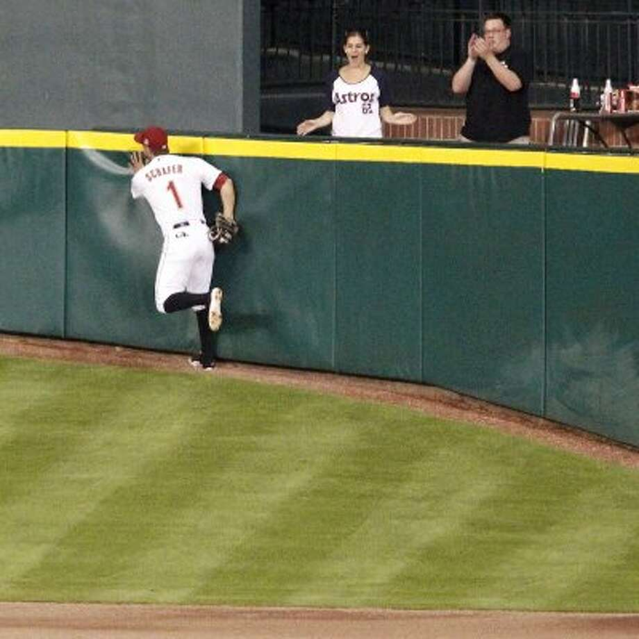Astros center fielder Jordan Schafer hits the outfield wall after catching a fly ball during the eighth inning. (James Nielsen / Chronicle)
