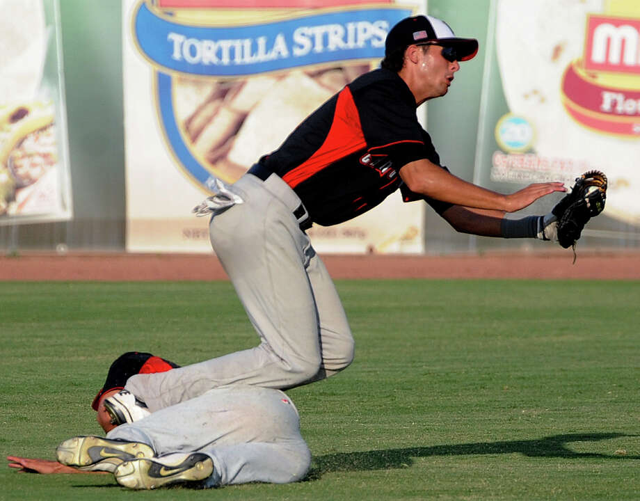 Lake Travis left fielder Ryan Lee makes a catch as he collides with centerfielder Dane Balaz during Class 4A regional finals baseball action against Boerne Champion at Wolff Stadium on Saturday, June 2, 2012. Photo: Billy Calzada, Express-News / © 2012 San Antonio Express-News