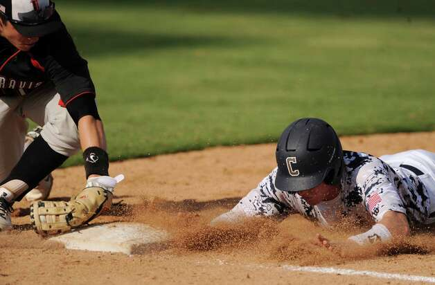 Josh Holcomb of Boerne Champion slides safely into first base as Baker Mayfield of Lake Travis attempts to tag him in a pick off attempt during Class 4A regional finals baseball action at Wolff Stadium on Saturday, June 2, 2012. Photo: Billy Calzada, Express-News / © 2012 San Antonio Express-News