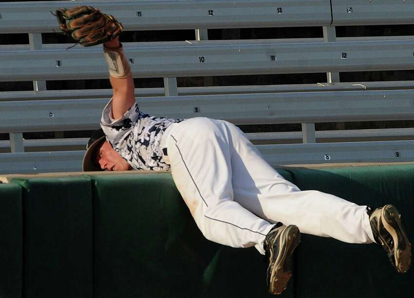Boerne Champion third baseman Josh Holcomb falls into the stands after catching a foul pop fly during Class 4A regional finals baseball action against Lake Travis at Wolff Stadium on Saturday, June 2, 2012.
