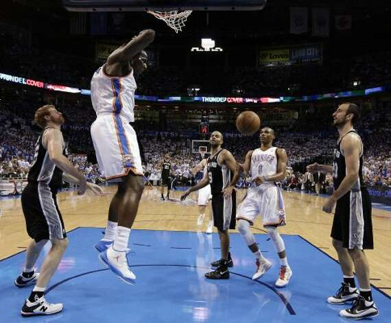 Oklahoma City Thunder's Kendrick Perkins (5) dunks near San Antonio Spurs' Matt Bonner (15) and San Antonio Spurs' Manu Ginobili (20) during the first half of game four of the NBA Western Conference Finals in Oklahoma City, Okla. on Saturday, June 2, 2012. (Kin Man Hui / San Antonio Express-News)