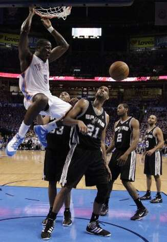 Oklahoma City Thunder's Kendrick Perkins (5) dunks near San Antonio Spurs' Tim Duncan (21) during the first half of game four of the NBA Western Conference Finals in Oklahoma City, Okla. on Saturday, June 2, 2012. (Kin Man Hui / San Antonio Express-News)