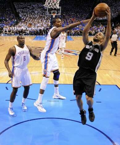 San Antonio Spurs' Tony Parker (9) shoots against Oklahoma City Thunder's Kevin Durant (35) and Oklahoma City Thunder's Kendrick Perkins (5) during the first half of game four of the NBA Western Conference Finals in Oklahoma City, Okla. on Saturday, June 2, 2012. (Edward A. Ornelas / San Antonio Express-News)