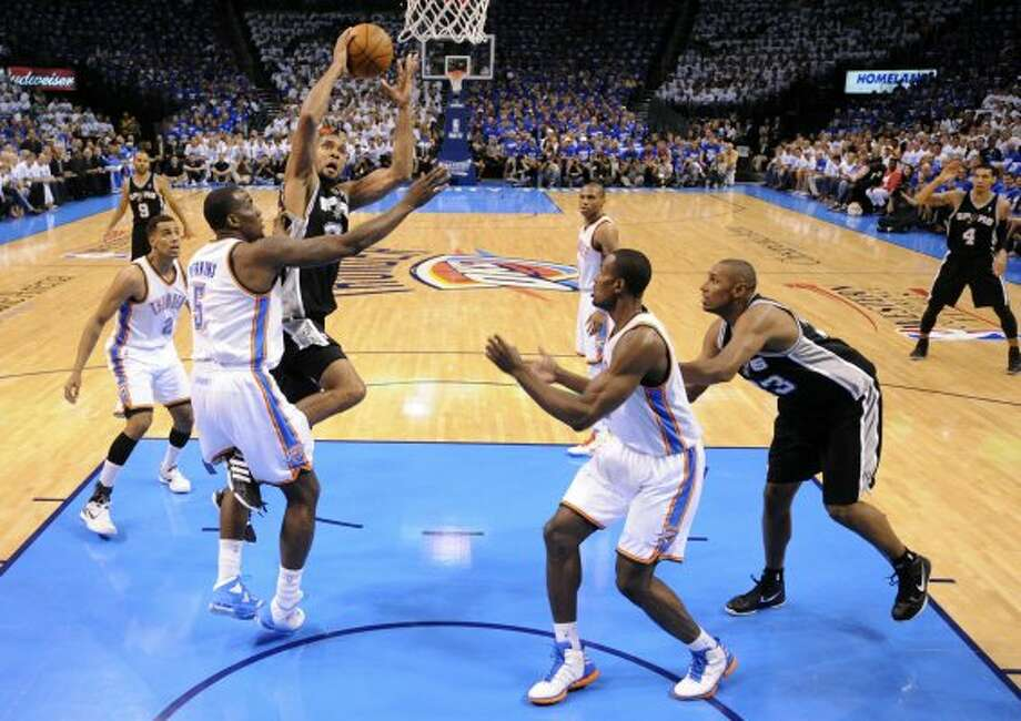 San Antonio Spurs' Tim Duncan (21) drives against Oklahoma City Thunder's Kendrick Perkins (5) during the first half of game four of the NBA Western Conference Finals in Oklahoma City, Okla. on Saturday, June 2, 2012. (Edward A. Ornelas / San Antonio Express-News)