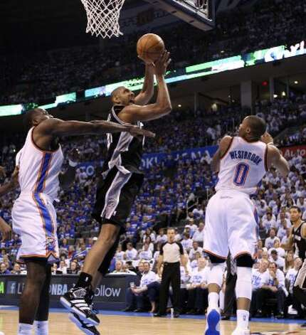 San Antonio Spurs' Tim Duncan (21) shoots against Oklahoma City Thunder's Kendrick Perkins (5) and Oklahoma City Thunder's Russell Westbrook (0) during the second half of game four of the NBA Western Conference Finals in Oklahoma City, Okla. on Saturday, June 2, 2012. (Edward A. Ornelas / San Antonio Express-News)