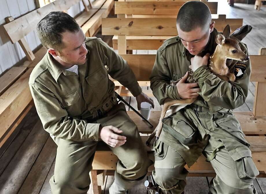 WWII re-enactors Brendan Schuller, left, and Matt Clausen, care for a baby deer that wondered onto a mock battlefield at Sommer Park in Peoria, Ill.,  during Saturday's Normandy WWII re-enactment, June 2, 2012. They later released the fawn, back into in the woods where it emerged during the mock battle. (AP Photo/Peoria Journal Star, Ron Johnson) Photo: Ron Johnson, Associated Press