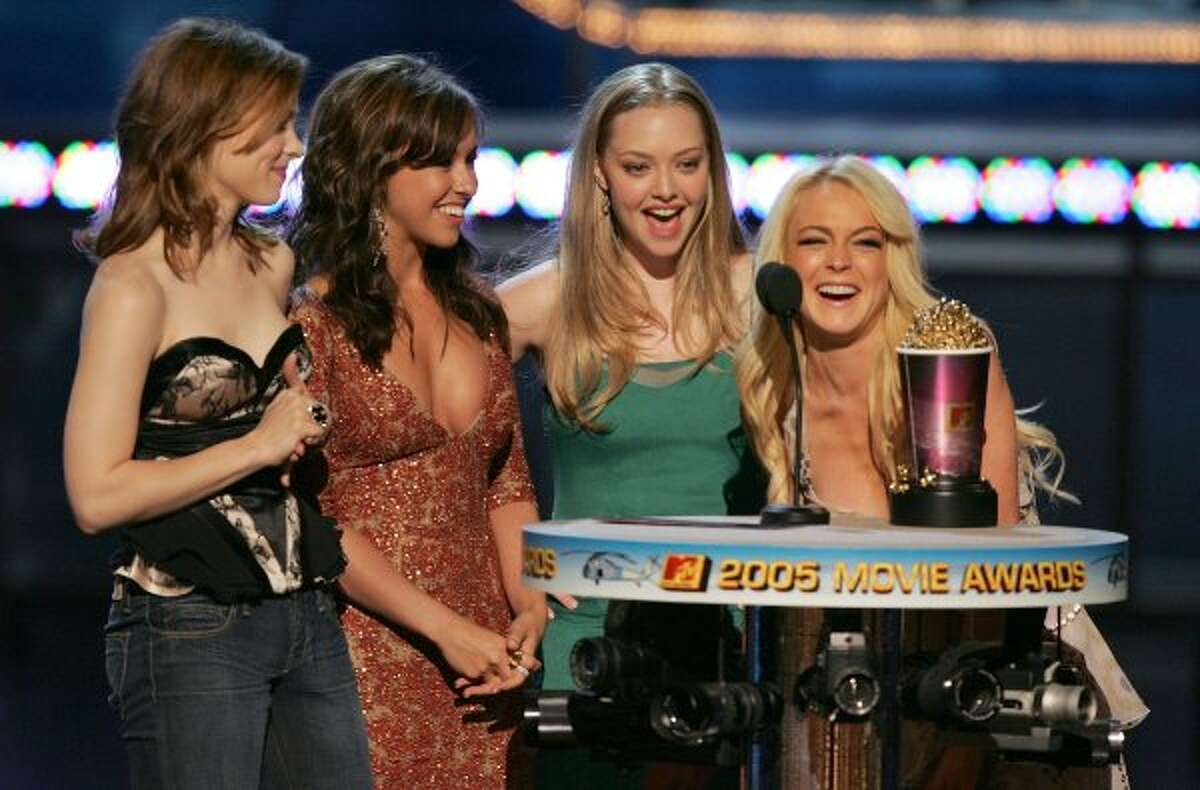 """The """"Mean Girls"""": Actresses Rachel McAdams, Lacey Chabert, Amanda Seyfried, and Lindsay Lohan accept their award for Best Team onstage during the 2005 MTV Movie Awards at the Shrine Auditorium on June 4, 2005 in Los Angeles, California. (Getty Images)"""