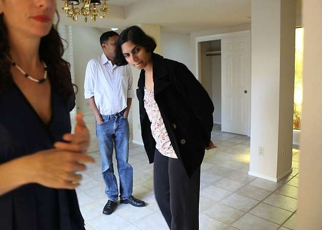 Buyer  Suhasini N. Ram (right) talking looking at the home with realtor Janelle Boyenga (far left) and her husband Sury Balasubramanian (back) in Sunnyvale, Calif., as they wait for the painter and contractor on Tuesday, May 15, 2012.  Suhasini and her husband beat out 14 other buyers in a multiple offer a few weeks ago, buying the townhome for 725K. Photo: Liz Hafalia, The Chronicle