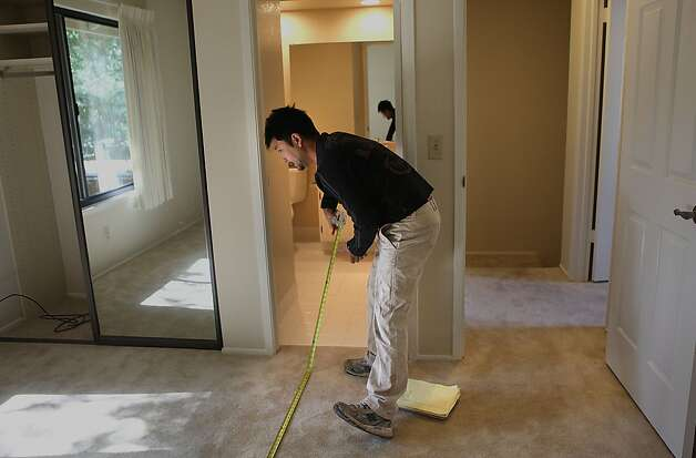 Painter Tony Lam of Total Hardwood Flooring taking measurements of a home in Sunnyvale, Calif.,  on Tuesday, May 15, 2012. Photo: Liz Hafalia, The Chronicle