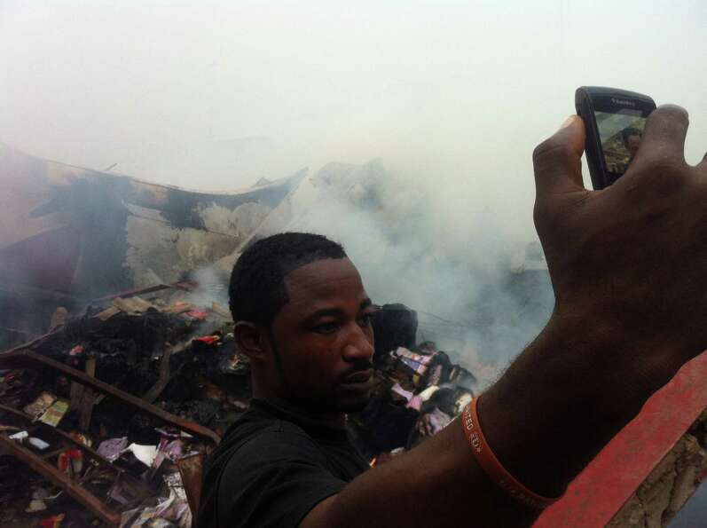 A man uses a cell phone to photograph himself in front of the wreckage of a passenger plane that cra