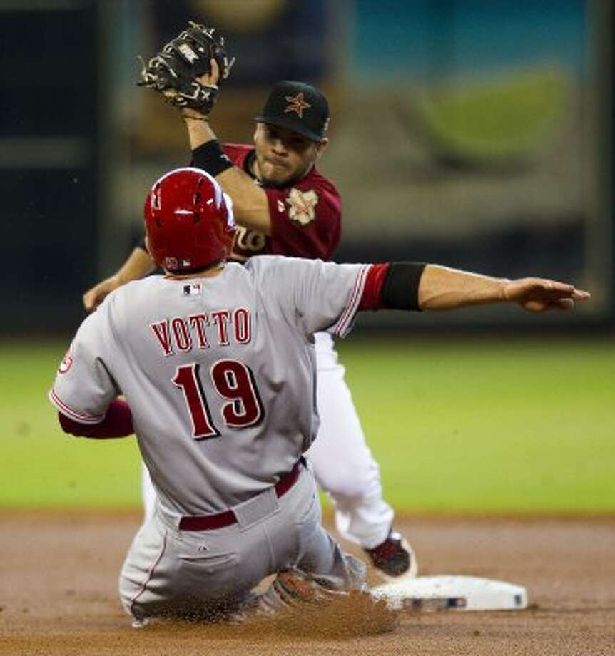 Astros second baseman Jose Altuve brings down a tag on Reds first baseman Joey Votto during an attempted steal. (Brett Coomer / Chronicle)