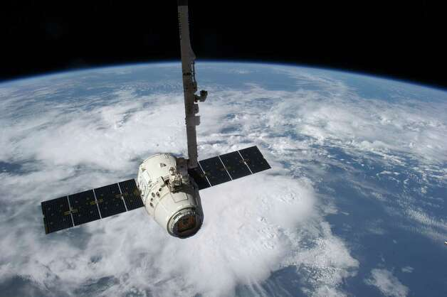 This image provided by NASA shows the SpaceX Dragon cargo craft just prior to being released by the International Space Station's Canadarm2 robotic arm (top center) on Thursday May 31, 2012 as it heads toward a splashdown in the Pacific Ocean. Photo: AP