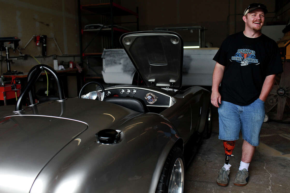Chris Leverkuhn, who was injured in Iraq, stands next to the Cobra he and other soldiers in the Automotivation program built at Lay'N Color in Converse, on Tuesday, May 15, 2012.