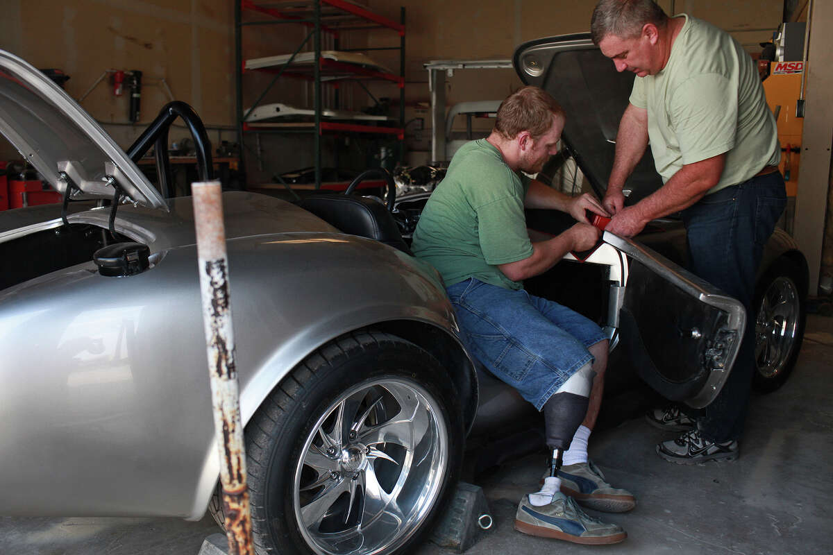 Chris Leverkuhn, who was injured in Iraq, left, works with Sgt. First Class Vic Hash, right, who was injured in Afghanistan, to get the Cobra running that they built with other soldiers with the Automotivation program at Lay'N Color in Converse on May 25, 2012 in preparation for taking it to the Helotes Memorial Day Car Show.
