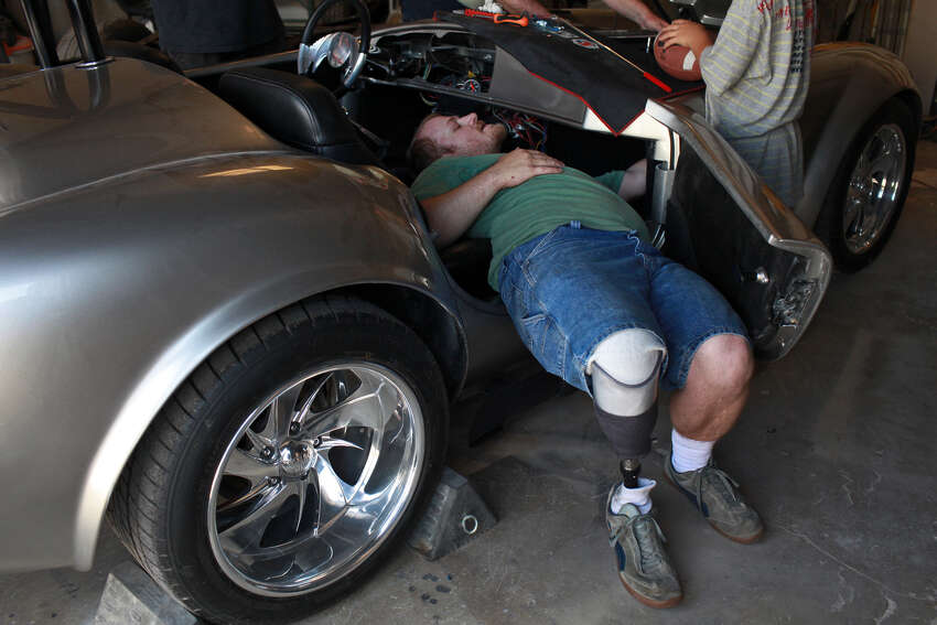 Chris Leverkuhn, who was injured in Iraq, works to get the Cobra he and other soldiers built with the Automotivation program running at Lay'N Color in Converse on May 25, 2012 in preparation for taking it to the Helotes Memorial Day Car Show.