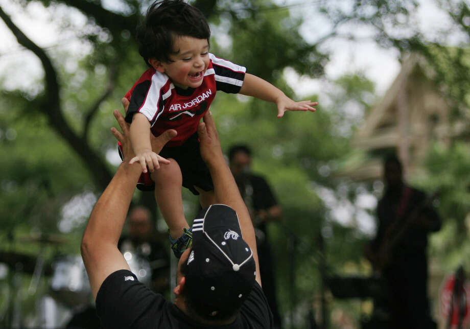 Juan Hernandez Jr., 1, laughs while his father throws him in the air during the 10th annual San Antonio Summer Art and Jazz Festival Sunday, June 3, 2012, at Crockett Park. Photo: Julysa Sosa, SAN ANTONIO EXPRESS-NEWS / SAN ANTONIO EXPRESS-NEWS