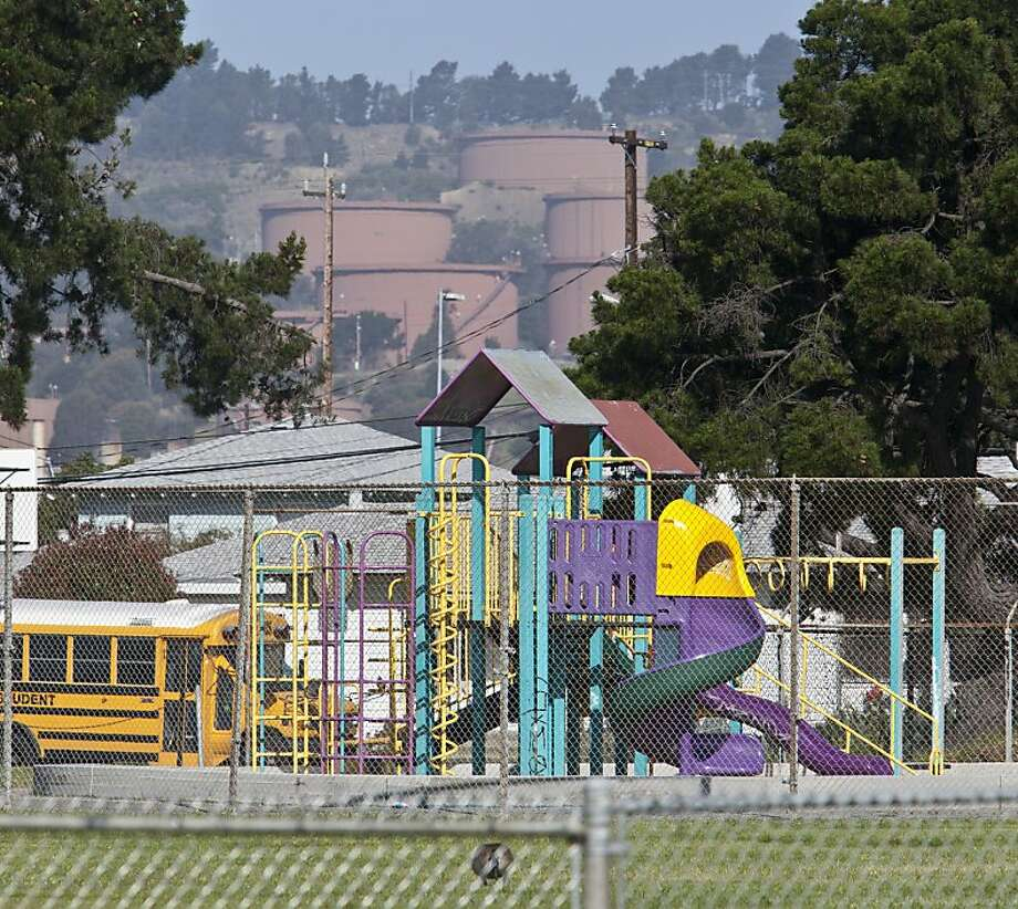 A play structure at a school in Atchison Village in North Richmond sits within view of Chevron storage tanks on May 8, 2012. Photo: Robert Durell