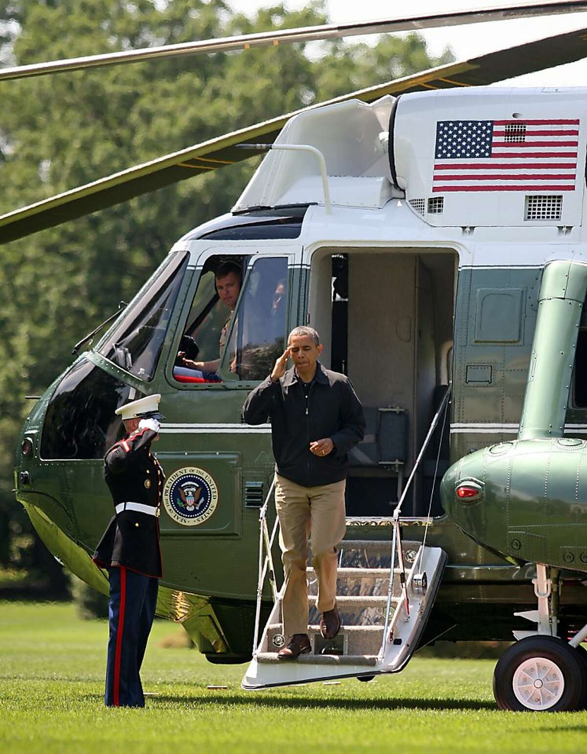 WASHINGTON, DC - JUNE 3: (AFP OUT) U.S. President Barack Obama salutes as he deboards Marine One on the South Lawn of the White House June 3, 2012 in Washington, DC. Obama was returning from from Camp David which since taking office he has visited 22 times. (Photo by Martin H. Simon-Pool/Getty Images)