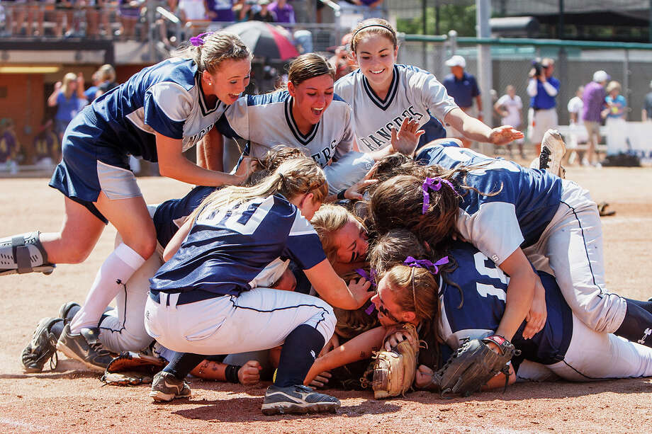 Smithson Valley softball players jump on first baseman Taylor Darilek after she made the final out in the Class 4A state championship game Saturday in Austin. Photo: MARVIN PFEIFFER, San Antonio Express-News / Express-News 2012
