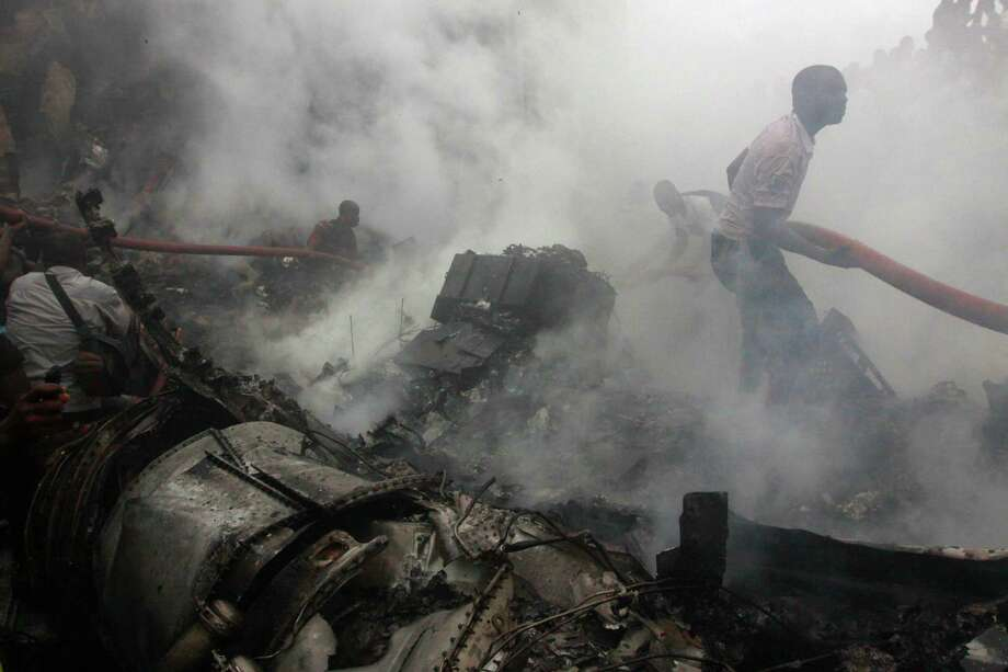 People gather at the site of a plane crash in Lagos, Nigeria, Sunday, June 3, 2012.  The passenger plane carrying more than 150 people crashed in Nigeria's largest city on Sunday, government officials said. Firefighters pulled at least one body from a building that was damaged by the crash and searched for survivors as several charred corpses could be seen in the rubble.(AP Photo/Sunday Alamba) Photo: Sunday Alamba, Associated Press / AP